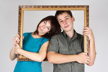 man and woman holding gold decorative frame and standing inside