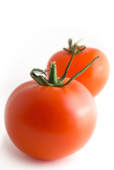 Two tomatoes, on white background, vertically.