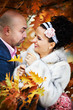 Joyful bride and groom in yellow autumn foliage