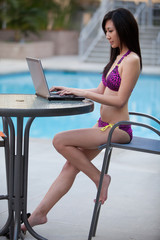 Asian Woman working on laptop by pool