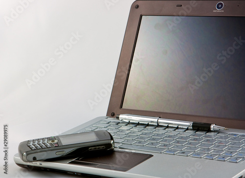 laptop, phone and pen on white background