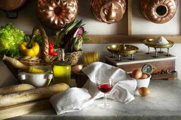 Tavolo della cucina  con verdura olio e bicchiere di vino