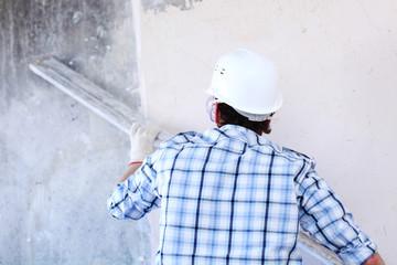 worker aligns wall