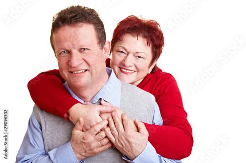 Ältere Frau umarmt ihren Mann von hinten