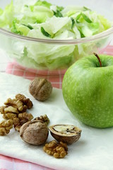 Mixed salad with green apple and walnuts on the table