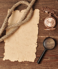old paper with pocket watch and magnifying glass