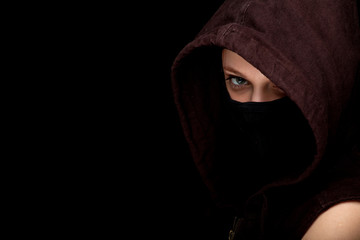 female thief in mask and hood, black background