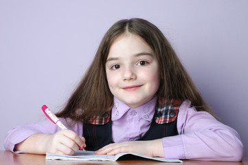 Little school girl doing homeworks at desk