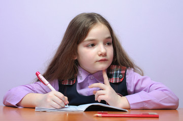 Thinking little school girl doing homeworks at desk