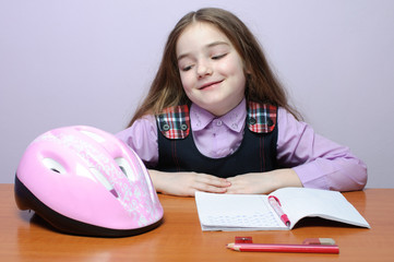 Happy little school girl doing homeworks at desk