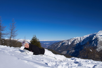 Cute tired snowboarder is resting on her snowboard