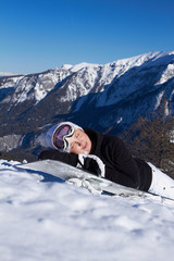A girl at the mountains in winter laying on snowboard