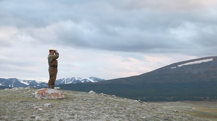 Hiker in mountain look into binoculars