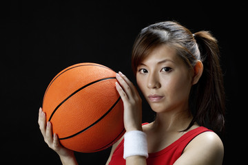 Young asian woman playing basketball