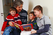 father reading a childrens book to his sons 02