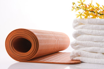 orange yoga mat, towel and orchid