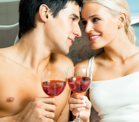 Young happy amorous couple with redwine at bedroom
