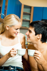 Young happy amorous couple drinking coffee together at home