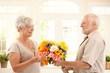 Senior man bringing flowers to wife