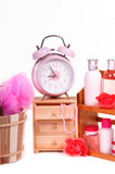 Pink alarm clock and a lot of pink bodycare accessories isolated poster