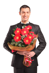 Handsome male wearing black suit and bow tie holding a bouquet o