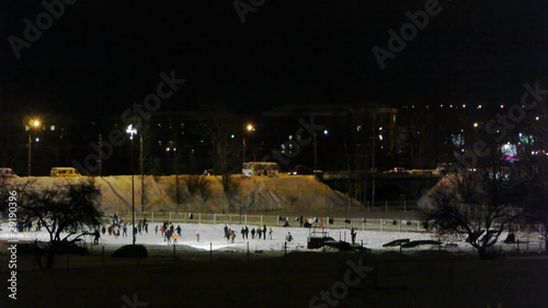 People skating on ice-rink, night panoramic view