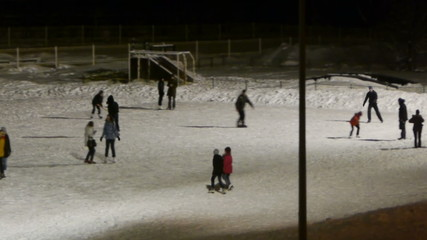 People skating on ice-rink, night panoramic view