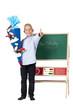 Junge mit Schultüte am Schulanfagn vor Tafel und zeigt Dau