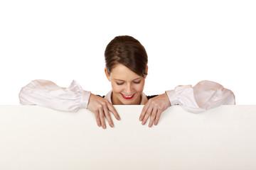Junge glückliche Frau blickt nach unten auf leeres Werbefläche