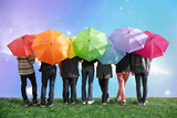 seven friends with rainbow color umbrellas on meadow collage