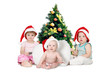 three chidren in christmas hats near Fur-tree