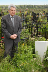 old sad senior in grey suit standing near grave with white grave
