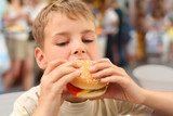 little caucasian boy eating burger, looking down