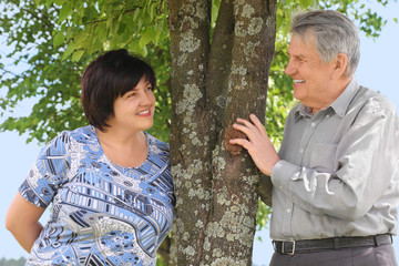 old senior and his adult daughter standing near tree and smiling