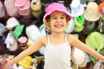 portrait of little girl trying pink panama in store and smiling,