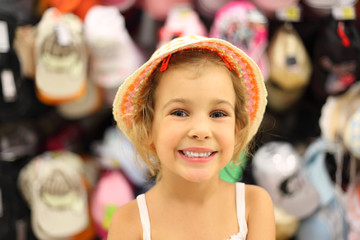 little girl trying panama in store and smiling