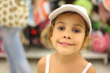 portrait of little girl trying white cap in store and smiling