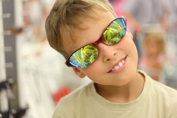 portrait of little boy trying sunglasses with reflection