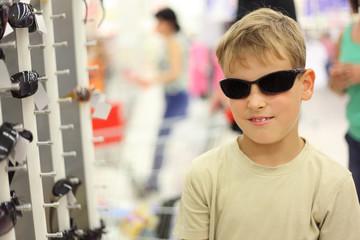 portrait of little boy trying black sunglasses in store