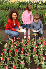 mother, son and daughter in greenhouse looking at tulips