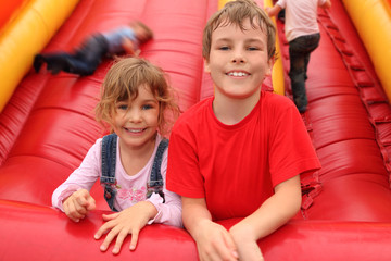 little boy and girl lying on red inflatable slide