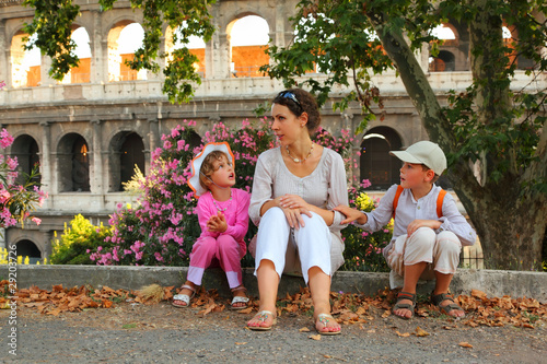 young mother, little son and daughter sitting near Colosseum