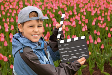 Boy with cinema clapper board standing on field with tulips