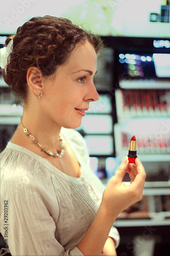beautiful young woman chooses red lipstick in store