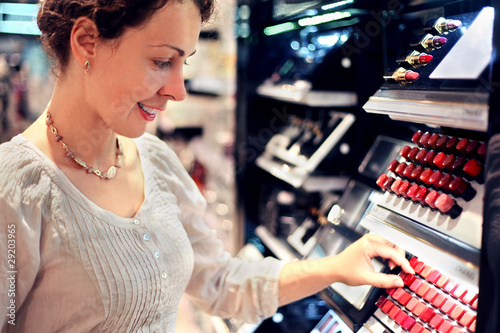 beautiful young woman chooses lipstick in store. big assortiment