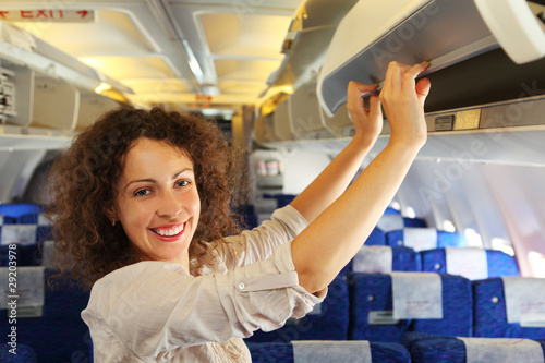 young woman on airplane adds baggage, rows of blue seats