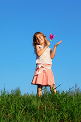 Smiling girl stands in field and knocks rattle in hand