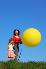 Mother and daughter in meadow, one of which inflates balloon