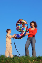 Mother and son standing and holding an inflatable figure of nine