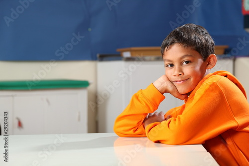 Schoolboy 10 wearing orange hoodie resting on classroom desk